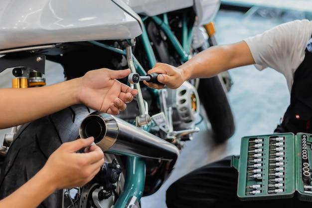 Mensen repareren een motorfiets gebruik een moersleutel en een schroevendraaier om te werken.