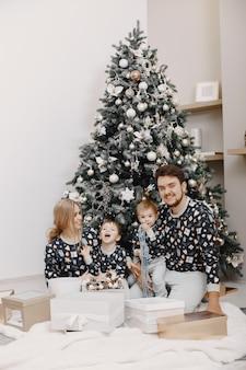 Mensen repareren voor kerstmis. mensen spelen met kind. familie rust in een feestelijke kamer.