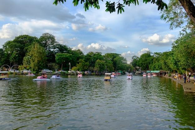 Mensen rijden waterfietsen of waterfiets bij meer met blauwe hemel