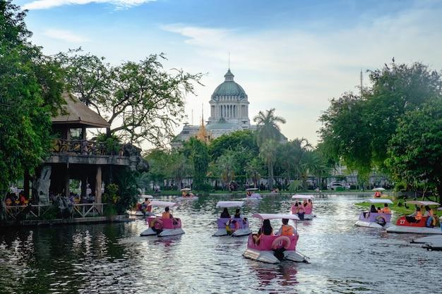 Mensen rijden waterfietsen of waterfietsen op het meer met the ananda samakhom throne hall