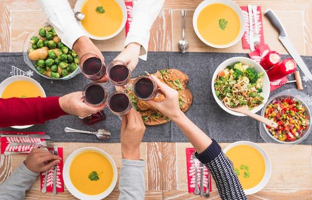 Mensen rinkelen glazen boven feestelijke tafel