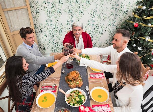 Mensen rinkelen glazen op kerst tafel