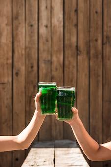 Mensen rinkelende glazen groene drankje in de buurt van de tafel