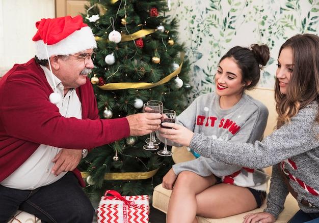 Mensen rinkelende wijnglazen dichtbij groene kerstboom