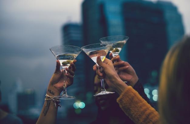 Mensen roosteren met cocktails op een feestje