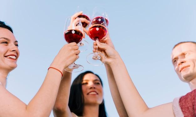 Mensen roosteren wijn in het zonlicht