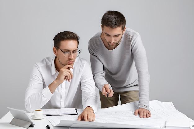 Mensen, samenwerking en discussieconcept. professionele architectmedewerkers kijken aandachtig naar de blauwdruk