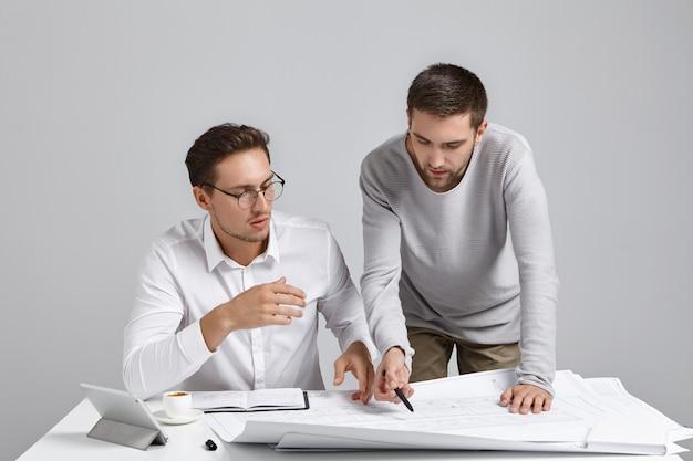 Mensen, samenwerking en teamwerkconcept. getalenteerde vakmensen werken aan tekeningen,