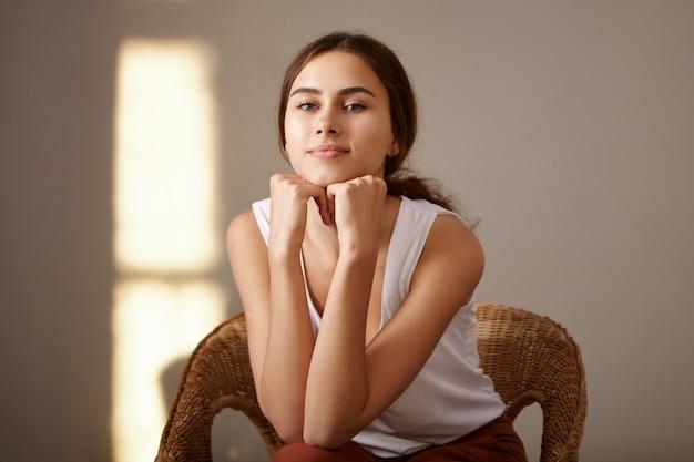 Mensen, schoonheid en jeugdconcept. indoor portret van charmante gebruinde slanke jonge europese vrouw ontspannen thuis zitten in geweven fauteuil alleen, handen onder haar kin. gouden uurzon