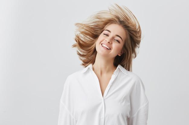 Mensen, schoonheid en lifestyle concept. ontsproten van vrij blond meisje met brede glimlach gekleed in wit overhemd, springend en spelend met haar haar. vrolijke en speelse blanke vrouw.