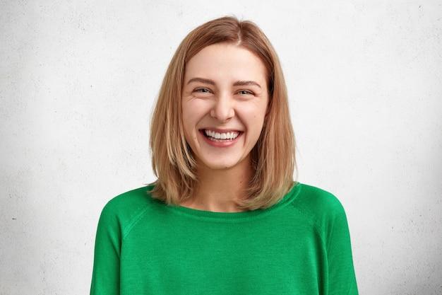 Mensen, schoonheid en positieve emoties concept. aantrekkelijke glimlachende jonge vrouw met afgeknipt kapsel, gekleed in groene casual sweater, blij om aanwezig te zijn