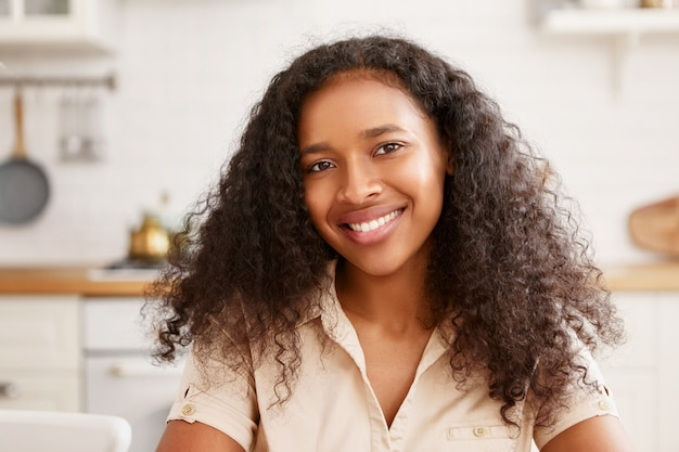 Mensen, schoonheid, etniciteit, vrouwelijkheid en positieve menselijke emoties. leuke mooie jonge afrikaanse vrouw met charmante stralende glimlach, verheugd over goed nieuws, ontbijten in gezellige keuken