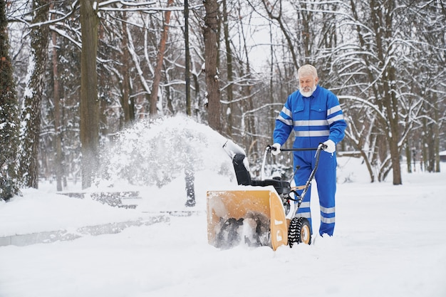 Mensen schoonmakende sneeuw met snowblover.