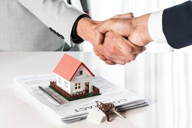 Mensen schudden handen over een speelgoedmodel huis