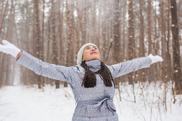 Mensen, seizoen en natuurconcept - aantrekkelijke vrouw in grijze vacht wandelen en veel plezier in de winter