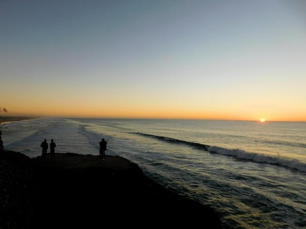 Mensen silhouet kijken zonsondergang op het strand