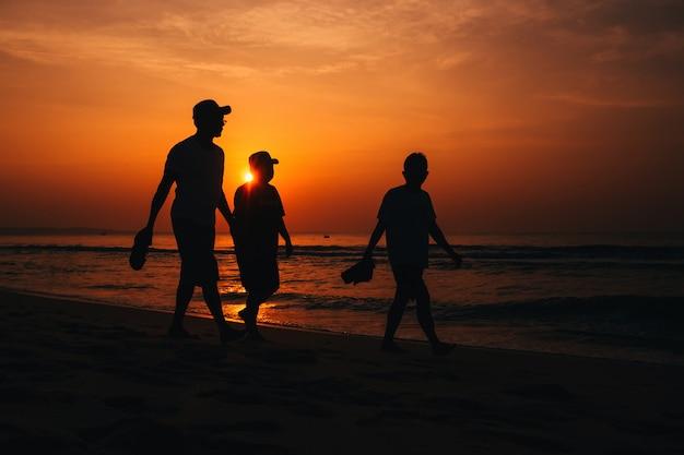 Mensen silhouetteren op het strand