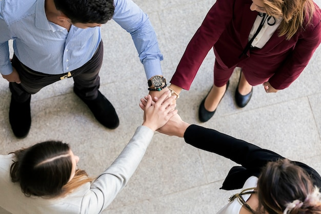 Mensen slaan de handen in elkaar tijdens teambuilding