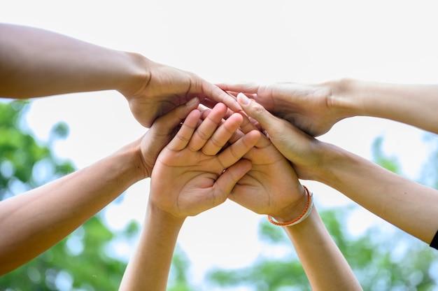 Mensen slaan de handen ineen om hun eenheid uit te drukken.