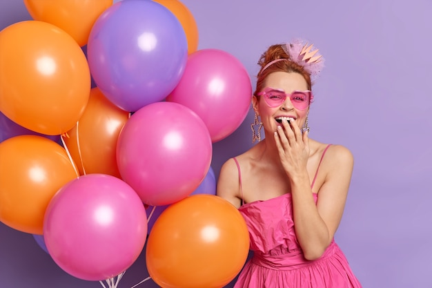 Mensen speciale gelegenheid vakantie stemming concept. positieve modieuze vrouw giechelt vrolijk voor mond, draagt zonnebril en feestelijke jurk houdt kleurrijke ballonnen vast