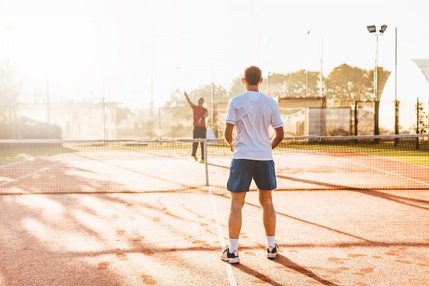 Mensen speeltennis in de ochtend in zonlicht