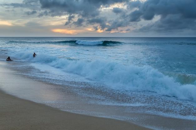 Mensen spelen op het strand met grote golven op de noordkust van oahu, hawaii