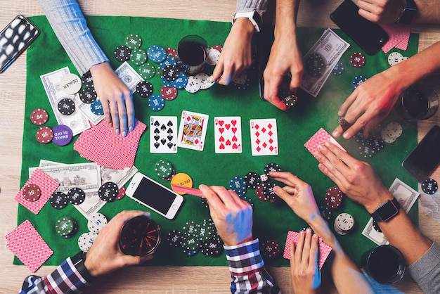 Mensen spelen poker op de tafel zijn kaarten en chips.