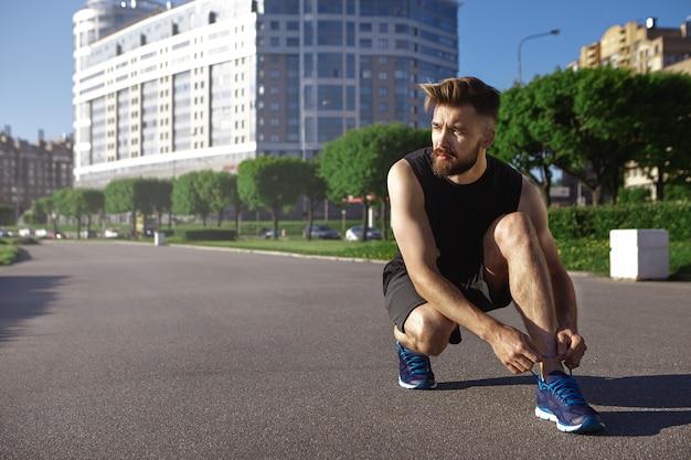 Mensen, sport, actieve levensstijl en fitnessconcept. portret van vermoeide jonge sportman met stijlvol kapsel en dikke baard rust tijdens cardio-oefening, zittend op beton en koppelverkoop schoenveters