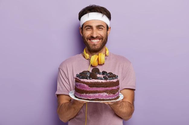 Mensen, sport en een goed voedingsconcept. vrolijke man met blije uitdrukking, houdt heerlijke cake vast, blij dat hij de kans heeft iets lekkers te eten, gemotiveerd is voor een gezonde levensstijl, houdt van aerobics