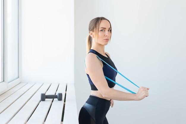 Mensen, sport en fitness concept - jonge vrouw training met training band in de sportschool.