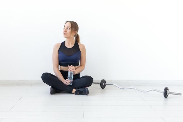 Mensen, sport en fitness concept - jonge vrouw zit met een fles water op gym mat. achtergrond met kopieerruimte