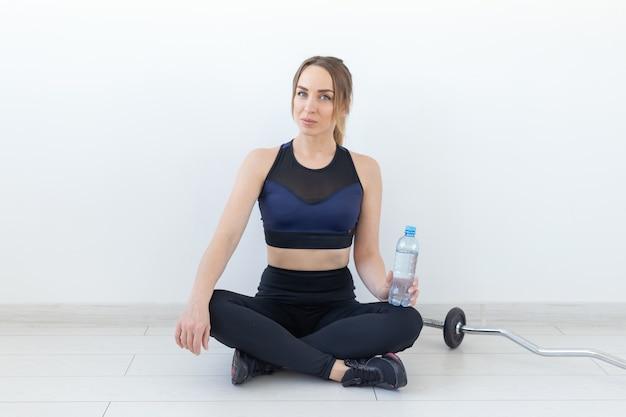 Mensen, sport en fitness concept - jonge vrouw zit met een fles water op gym mat.