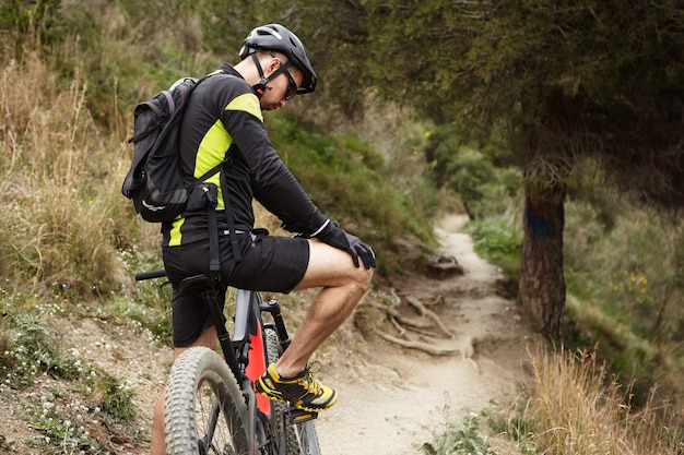 Mensen, sport, extreme en reizen concept. jonge blanke mannelijke ruiter in wielerkleding met een paar minuten pauze tijdens outdoor training in de ochtend, oefenen op zijn booster fiets