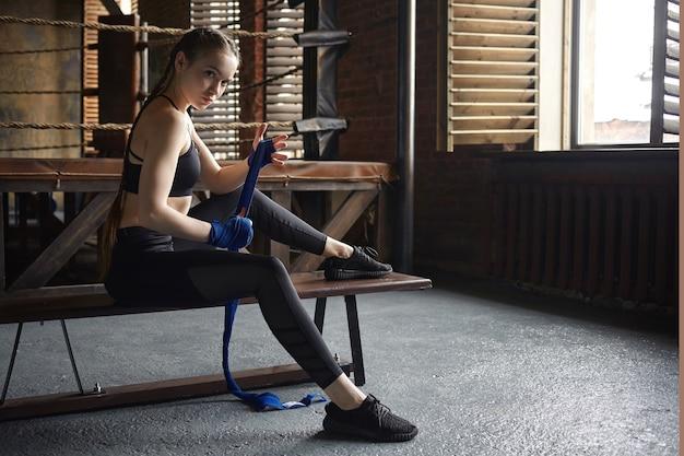 Mensen, sport, fitness, activiteit en gezondheidsconcept. actieve atletische jonge europese vrouw, gekleed in zwarte sneakers en sportkleding