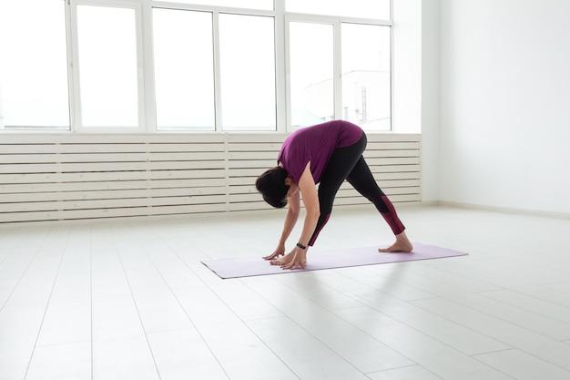 Mensen, sport, yoga en gezondheidszorg concept - zijaanzicht van een vrouw die zich uitstrekt naar beneden leunen