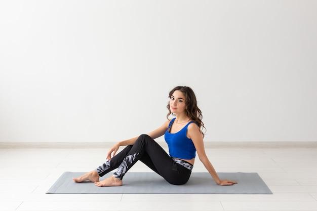 Mensen, sport, yoga en gezondheidszorgconcept. glimlachende jonge vrouwenzitting op oefeningsmat.