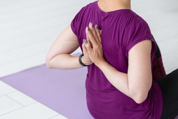 Mensen, sport, yoga en gezondheidszorgconcept - vrouwenzitting van middelbare leeftijd op yogamat met handen achter haar rug