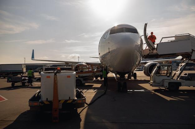 Mensen staan in de buurt van een groot modern vliegtuig en bereiden het voor op het instappen in de luchthavenhub overdag. vliegtuig, verzending, transportconcept
