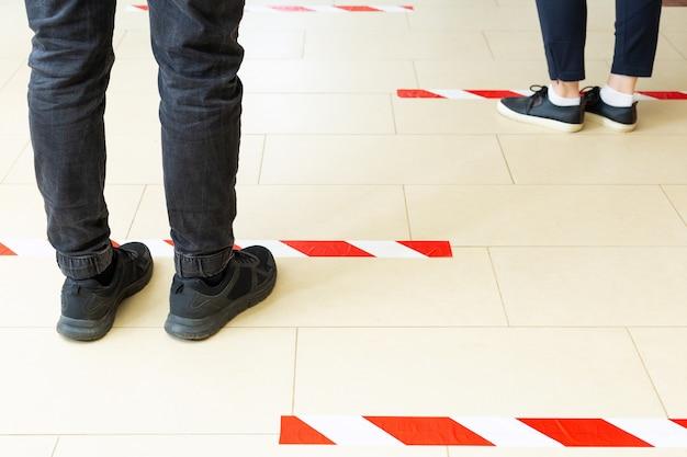 Mensen staan in de rij en houden sociale afstand, staan achter een waarschuwingslijn tijdens covid 19 coronavirus quarantaine. veilig winkelen, sociaal afstandsconcept. benen in de rij close-up