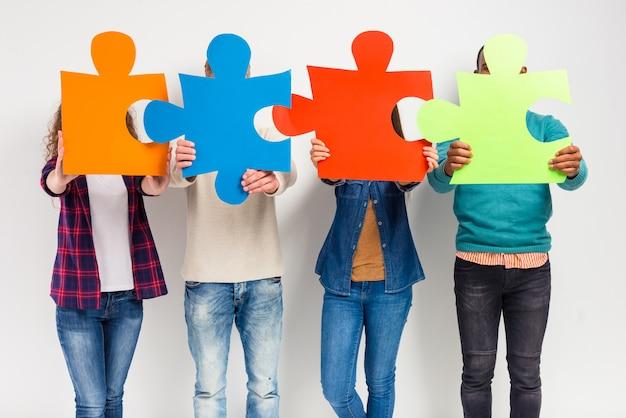 Mensen staan met puzzels in de buurt van hun gezichten.