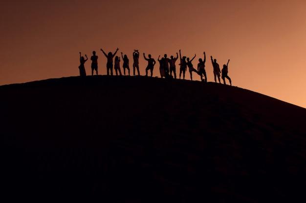 Mensen staan op de top van duin in de woestijn met handen omhoog. silhouetten bij zonsondergang.