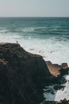 Mensen staan overdag op een klif
