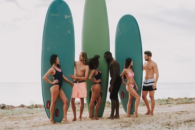 Mensen staan strand houdt surfs meisjes in zwempakken