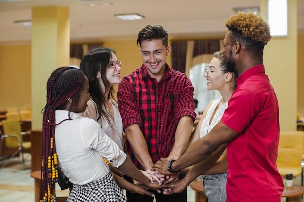 Mensen stapelen handen die elkaar ondersteunen