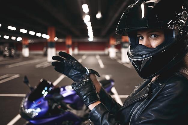 Mensen, stedelijke levensstijl, extreme sporten en adrenaline. zijwaarts portret van palyful styligh jonge blanke motorrijder in modieus zwart lederen jas en helm, handschoenen aan te passen
