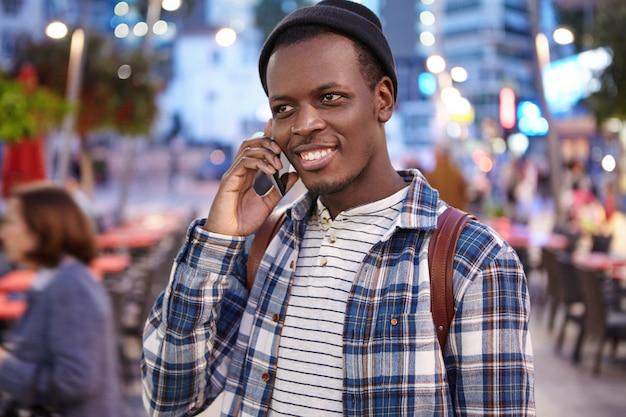 Mensen, stedelijke levensstijl, moderne technologie en communicatieconcept. openluchtportret van knappe trendy uitziende jonge zwarte mens die nacht van wandeling rond stad genieten, die op mobiele telefoon aan zijn vriend spreken