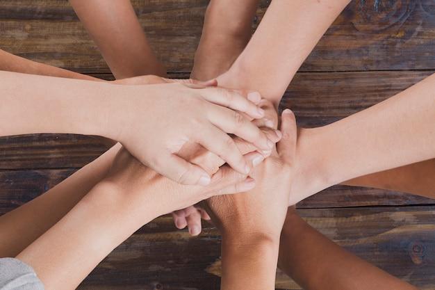 Mensen stellen hand samen voor gebruik als eenheidsgroepswerkconcept