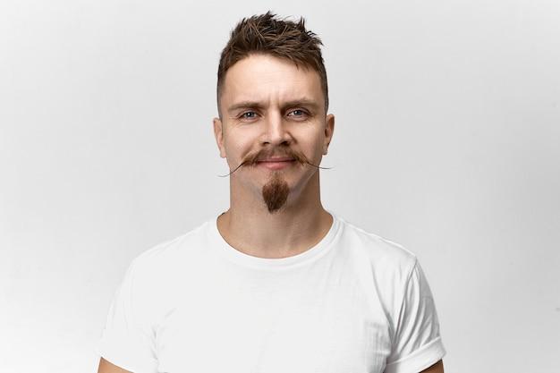 Mensen, stijl, kappers en mode-concept. geïsoleerd schot van gelukkige vrolijke jonge europese hipster kerel die lacht, zich verheugt op zijn nieuw stijlvol kapsel, snor en baard bij kapperszaak