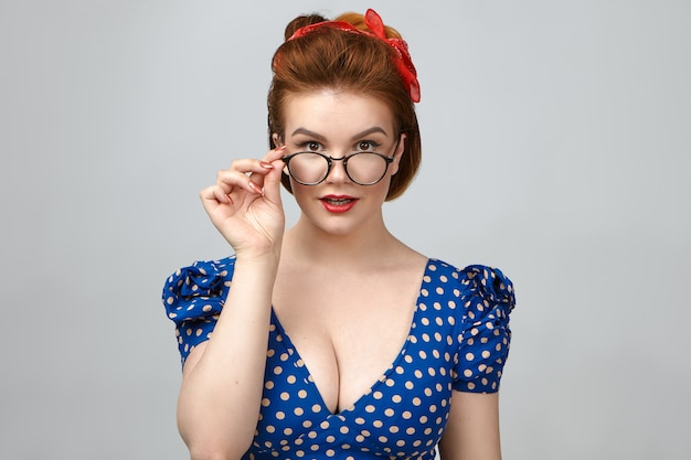 Mensen, stijl, mode, optiek en brillen. geïsoleerde schot van prachtige pin-up girl model in laag uitgesneden jurk reclame bril in studio, hand houdend op stijlvolle bril en glimlachend in de camera