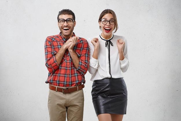 Mensen, succes, geluk concept. mooie vrouw en onhandige bebaarde man kijken vreugdevol,